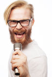 Young man with a beard holding a microphone Stock Image