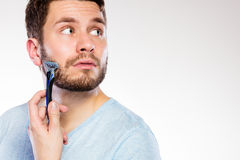 Young man with beard holding razor blade Stock Photography
