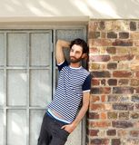 Young man with beard leaning against wall outdoors Stock Photos