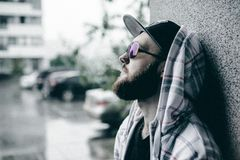 Man with beard in light checkered jacket with hood in a cap and sunglasses walking freely around city smokes an e-cigarette