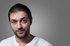Young man with beard with a little smile. On grey background Royalty Free Stock Images