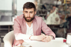 Young man with beard looking at camera. Handsome young elegant man sitting, relaxing, smiling. Men with beard looking at camera. Indoor photo Royalty Free Stock Photos