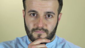 A young man with a beard looking at camera stock footage