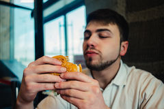 A young man with a beard looking at going to a burger and eat it. A young man with a beard looking at tasty burger and eat it going Royalty Free Stock Image