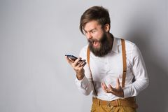 A young man a beard. A man with a beard in a white shirt and yellow suspenders shouts in the phone indignantly trying to explain his idea on gray background stock photography