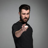 Young man with beard and mustaches, finger. Pointing towards the camera on a gray background royalty free stock photo
