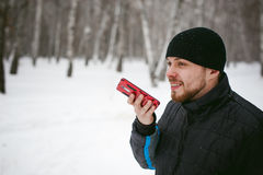 Young man with a beard outdoors in the snow in the winter. A young man with a beard, smokes an electronic cigarette and happily talking on the phone through the Stock Photo