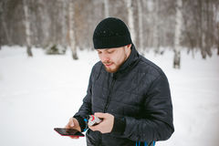 Young man with a beard outdoors in the snow in the winter. A young man with a beard, smokes an electronic cigarette and happily talking on the phone through the Royalty Free Stock Photography