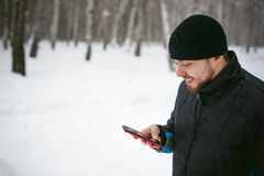 Young man with a beard outdoors in the snow in the winter Stock Image