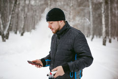 Young man with a beard outdoors in the snow in the winter. A young man with a beard, smokes an electronic cigarette and happily talking on the phone through the Stock Images