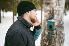 Young man with a beard outdoors in the snow in the winter. A young man with a beard, smokes an electronic cigarette and happily talking on the phone through the Stock Image