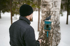 Young man with a beard outdoors in the snow in the winter. A young man with a beard, smokes an electronic cigarette and happily talking on the phone through the Stock Photography