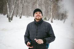 Young man with a beard outdoors in the snow in the winter. A young man with a beard, smokes an electronic cigarette and happily talking on the phone through the Royalty Free Stock Images