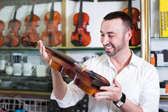 Young man with beard purchasing traditional violins Stock Image
