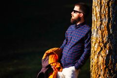 Young man with beard resting on a plant.  Stock Image