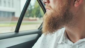 A young man with a beard rides in the back seat of the car. stock image