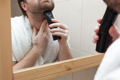 Young man with a beard shave stubble with electric razor. Royalty Free Stock Images
