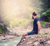 Young man with a beard and short hair, sitting on the bank of a mountain river in shorts and a blue shirt, with natural nature bac Royalty Free Stock Photos