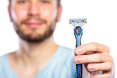 Young man with beard showing razor blade Stock Images