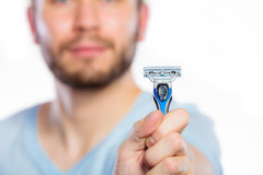 Young man with beard showing razor blade Stock Image