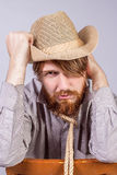 Young man with a beard is sitting on a brown chair Royalty Free Stock Photo