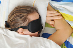 Young man  with beard sleeping with sleep mask in bed Stock Photo