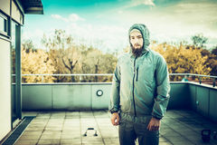 Young man with  beard in a sports suit, standing on the terrace of the house, on the background  sports equipment, and the type Royalty Free Stock Photos