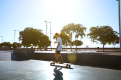 Young man with beard and tattoos skating on longboard royalty free stock photos