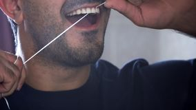 Young man with beard is using dental floss to clean his teeth. Close-up of man flossing his teeth. Mouth health care royalty free stock photos