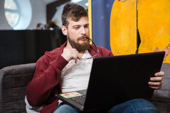 Young man with beard using laptop and holding glasses. Young handsome man with beard in brown hoodie sitting on sofa, using laptop and holding glasses Royalty Free Stock Photo
