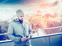 Young man with a beard, wearing a gray tracksuit, standing on the terrace of the house, on  background of sunset sky and cityscap Stock Image