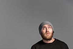 A young man with a beard wearing a hat on a gray background Royalty Free Stock Photos