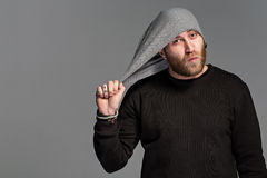 A young man with a beard wearing a hat on a gray background Stock Photo
