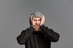 A young man with a beard wearing a hat on a gray background Stock Photography