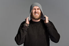 A young man with a beard wearing a hat on a gray background Royalty Free Stock Images