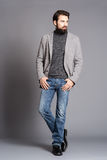 A young man with a beard, wearing a jacket and jeans standing Stock Image