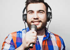 Young man with a beard wearing a shirt holding a microphone Stock Photo