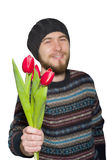 A young man with a beard wearing a sweater and hat with red tulips. Isolated on white background Stock Photography