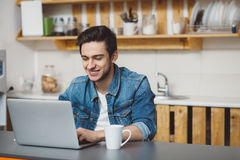 Young man with beard working on laptop. Happy guy is sitting in the kitchen and chatting with his friends Stock Photo