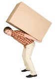 Young man bears the big box on a back. The young man bears the big box on a back Royalty Free Stock Photography
