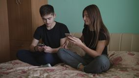Young man and beautiful girl sitting in a room with blue walls and playing with a mobile phone. royalty free stock photo