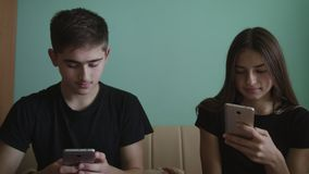 Young man and beautiful girl sitting in a room with blue walls and playing with a mobile phone. stock image