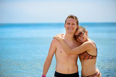 Young man and beautiful girl smiling at ocean beach Royalty Free Stock Photos