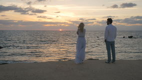 Young man and beautiful woman enjoys the sea sunset. Young woman in long dress stands on the beach and enjoys the sea sunset. Handsome man come to the girl and stock video