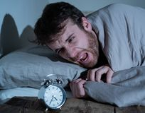 Young man in bed with alarm clock feeling desperate and distress not able to sleep with insomnia. Mental health, Insomnia and sleeping disorders. Frustrated and stock images