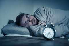 Young man in bed with alarm clock feeling desperate and distress not able to sleep with insomnia. Mental health, Insomnia and sleeping disorders. Frustrated and royalty free stock photo