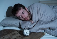 Young man in bed with alarm clock feeling desperate and distress not able to sleep with insomnia. Mental health, Insomnia and sleeping disorders. Frustrated and stock image