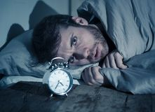 Young man in bed with alarm clock feeling desperate and distress not able to sleep with insomnia. Mental health, Insomnia and sleeping disorders. Frustrated and royalty free stock photography