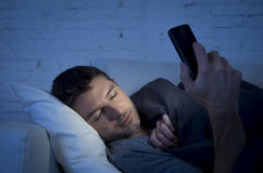 Young man in bed couch at home falling asleep late at night while using mobile phone in low light Stock Images