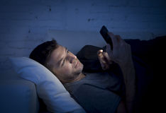 Young man in bed couch at home late at night texting on mobile phone in low light relaxed. In communication technology and internet social network concept royalty free stock image